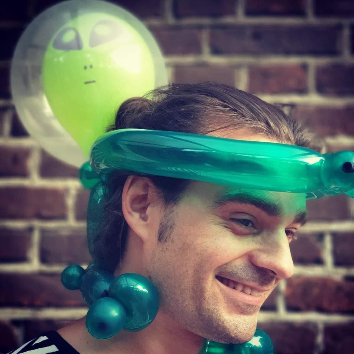 lachender Mann mit Ballon auf dem Kopf in Form eines Aliens