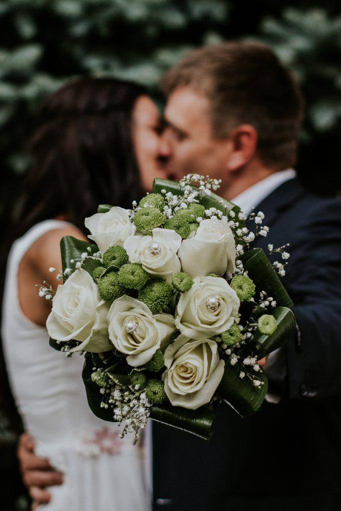 Hochzeitspaar küsst sich und halten weißen Rosenstrauß in den Händen