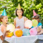 4 Kinder mit Partyhüten und Ballons spielen draußen und lachen