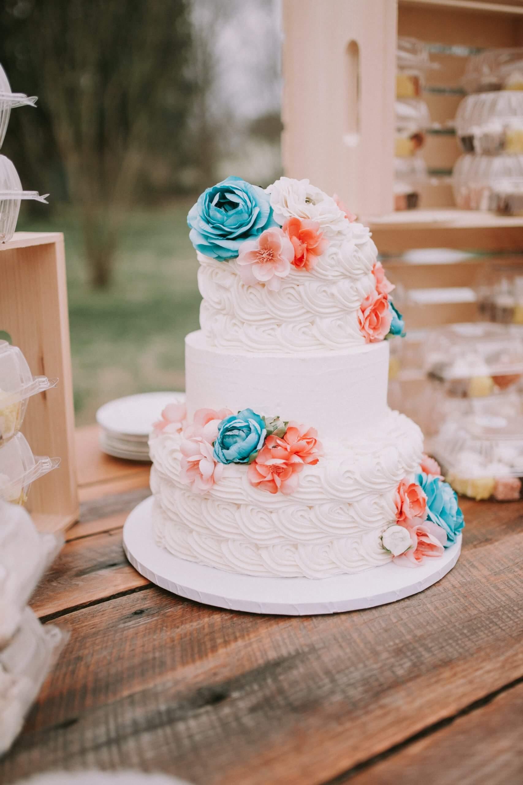 Schöne Hochzeitstorte mit roten und blauen Marzipanrosen. Die Torte steht auf einem Holztisch draußen im freien