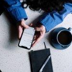 Mann im blauen Hemd setzt mit Smartphone an einem Tisch. Auf dem Tisch steht eine Tasse Kaffee und ein Notizbuch.