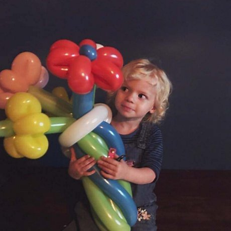 ein Kind mit bunten Blumen Ballons in der Hand